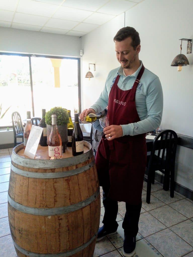 Photo de maxime bourdel en train d'exercer son metier de sommelier et conseiller sur les vin en accord avec les mets et plats